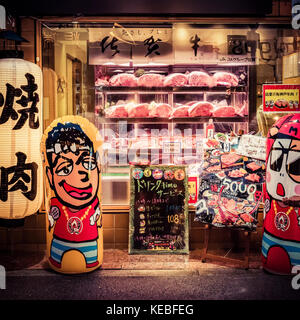 The bright window of a butchers shop in downtown Osaka drawing in customers - Stock Image