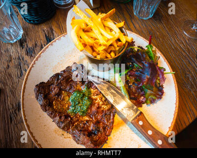Lunchtime flattened pan-seared bavette Steak served with French fried potatoes and rocket salad showing steak knife. - Stock Image