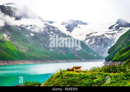 Solitude at high mountain valley. Quiet spot near mountain lake and snowy peaks of Alps; Scenic view to alpine nature - Stock Image