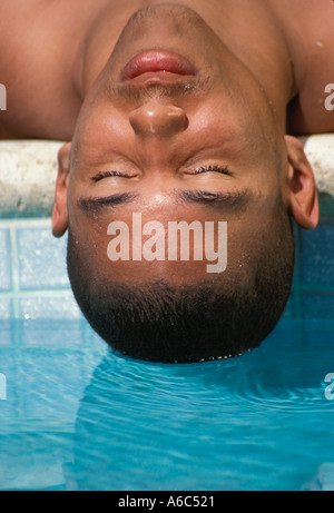 African American Male Teen Face over swimming pool - Stock Image