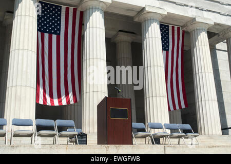 American flags behind podium on stage outdoors - Stock Image