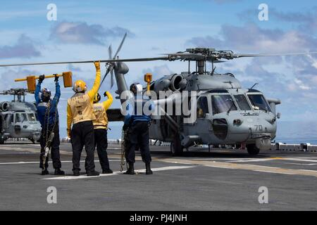 180827-N-KW492-0057 ATLANTIC OCEAN (Aug. 27, 2018) Sailors signal to the crew of a MH-60S Sea Hawk during flight operations on the flight deck aboard the Wasp-class amphibious assault ship USS Kearsarge (LHD3) during the Carrier Strike Group FOUR (CSG 4) Amphibious Ready Group, Marine Expeditionary Unit Exercise (ARGMEUEX). Kearsarge Amphibious Ready Group and 22nd Marine Expeditionary Unit are enhancing joint integration, lethality and collective capabilities of the Navy-Marine Corps team through joint planning and execution of challenging and realistic training scenarios. CSG 4 mentors, trai - Stock Image
