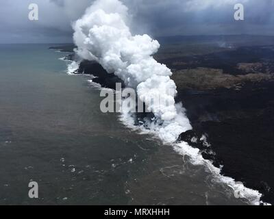 Lava and poisonous sulfur dioxide plumes rise as molten magma reaches the ocean from the eruption of the Kilauea volcano May 26, 2018 in Pahoa, Hawaii. Hot lava entering the ocean creates a dense white plume called 'laze' (short for 'lava haze'). Laze is formed as hot lava boils seawater to dryness. The process leads to a series of chemical reactions that create a billowing white cloud composed of a condensed seawater steam, hydrochloric acid gas, and tiny shards of volcanic glass. The cloud is as corrosive as dilute battery acid, and should be avoided. - Stock Image