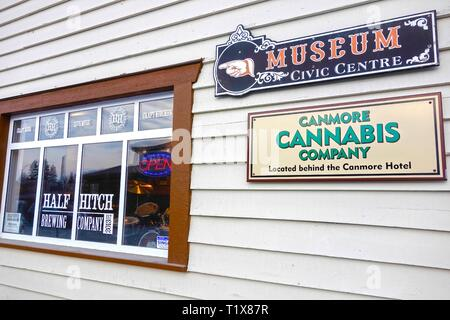 Historic Canmore Hotel, home to Half Hitch Brewing Company from Cochrane, Alberta with Direction Signs to Museum Civic Centre and Cannabis Company - Stock Image