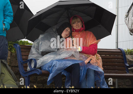 Portsmouth, UK. 26th July 2015. Spectators shelter from the wind and the rain waiting for the second day of racing - Stock Image