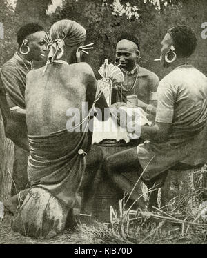 Four men playing cards in Kenya (then a British colony), East Africa. - Stock Image