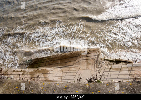 The high tide at Ramsgate lapping on the promenade steps to the sandy beach. - Stock Image