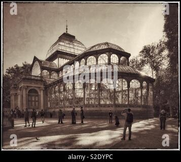 A retro effect image of visitors walking around The Palacio de Cristal (Crystal Palace) in Madrid's Buen Retiro Park - a must see architectural structure. Photo © COLIN HOSKINS. - Stock Image
