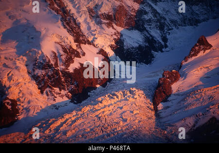 Alpenglow colours La Jonction and the Glacier des Bossons pink, with the Grands Mulets mountain hut visible on the rock island - Stock Image