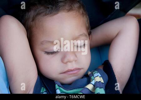 toddler asleep in pram - Stock Image