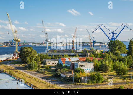 Warehouses and dock with yellow, blue and orange gantry cranes, Port of Warnemunde, Germany, Europe - Stock Image