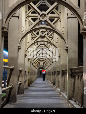 A man stands on the path of repeating iron arches that supports the River Tyne's High Level Bridge between Newcastle and Gateshead. - Stock Image