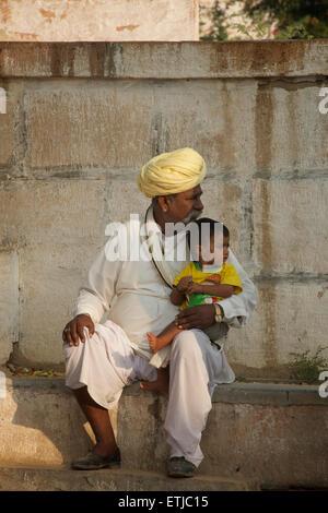 Rajasthani man in white with distinctive turban and child. Rural village near Jodhpur, Rajasthan, India. - Stock Image