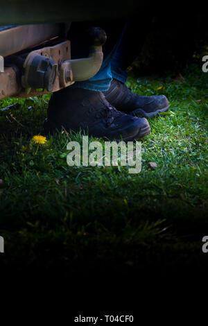 mysterious boots of a man standing behind a truck-  image for book cover - Stock Image