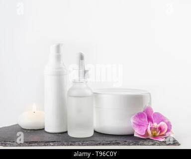 Different material shape and size cosmetic product cream, oil containers on white background standing on black stone base, pink orchid blossom. - Stock Image