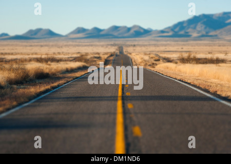 A long road through the desert in Arizona at sunset - Stock Image