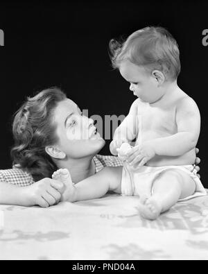 1940s ALERT BABY DAUGHTER SITTING UPRIGHT LOOKING FACE TO FACE AT EXPRESSIVE MOTHER WHO IS PINCHING HER FOOT - b2521 HAR001 HARS JUVENILE FACIAL COMMUNICATION YOUNG ADULT TEAMWORK INFANT STRONG JOY LIFESTYLE FEMALES HOME LIFE FULL-LENGTH LADIES PHYSICAL FITNESS DAUGHTERS PERSONS CARING EXPRESSIONS B&W IS UPRIGHT HAPPINESS HEAD AND SHOULDERS AT LOVING FACE TO FACE WHO CONNECTION EYE TO EYE ALERT CURIOUS STYLISH PERSONAL ATTACHMENT AFFECTION EMOTION JUVENILES MOMS TOGETHERNESS YOUNG ADULT WOMAN BABY GIRL BLACK AND WHITE CAUCASIAN ETHNICITY EXPRESSIVE HAR001 INQUISITIVE OLD FASHIONED - Stock Image