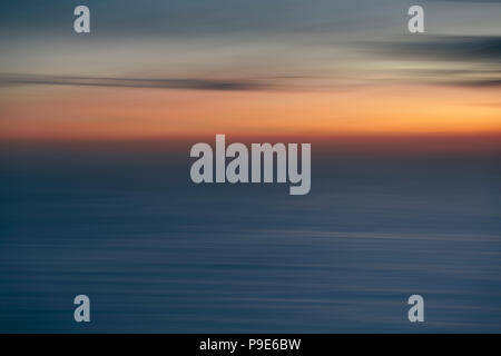 View out to sea over the ocean at dusk,  the sunset light on the horizon and calm undulating sea surface. Abstract coloured light effect. - Stock Image