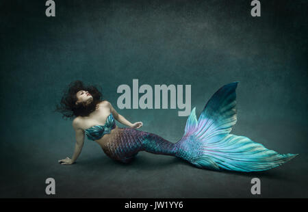 Mermaid with iridescent tail underwater in a pool - Stock Image