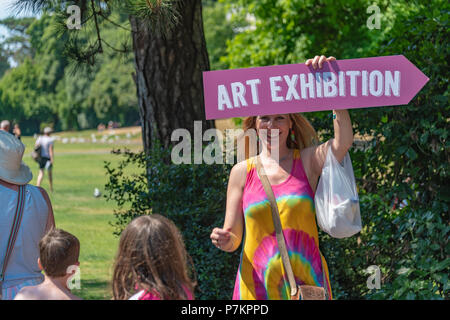 Bournemouth, UK. 7th July 2018. Woman holds a sign to an Art Exhibition in Bournemouth during the July heatwave. Credit: Thomas Faull / Alamy Live News - Stock Image