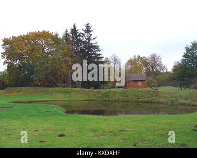 Rural autumn landscape with trees pond and small wooden barn - Stock Image