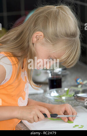 Young girl cutting celery on the bias - Stock Image