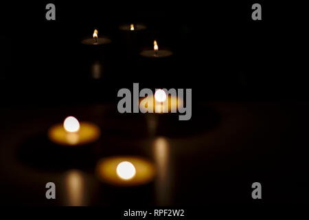 Playing with a minimum of light and bokeh effect, candles lights are reflecting shadows and toughts. - Stock Image