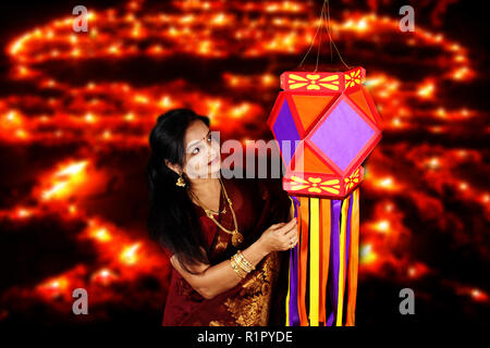 An Indian middleaged woman admiring the traditional lantern in her house, on the eve of Diwali festival in India. - Stock Image
