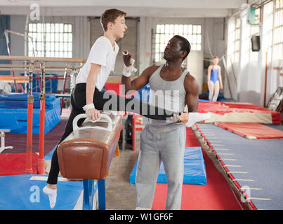 African male coach helping teenage boy doing gymnastic exercises on equipment - Stock Image
