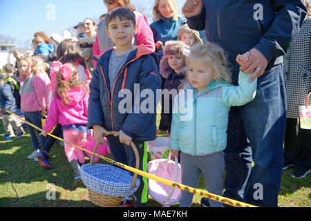 North Merrick, New York, USA. March 31, 2018. Young girls and boys eagerly wait behind yellow tape for start of traditional Easter Egg Hunt at the Annual Eggstravaganza, held at Fraser Park and hosted by North and Central Merrick Civic Association (NCMCA). Credit: Ann E Parry/Alamy Live News - Stock Image