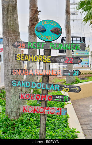 Colorful directional sign or signs pointing to charter fishing boat slips for the commercial fishing fleet at HarborWalk Marina in Destin Florida USA. - Stock Image
