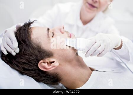 Dermatologist applying facial microdermabrasion treatment on man in clinic, close-up. The cosmetic procedure uses micro crystals to remove dead skin c - Stock Image
