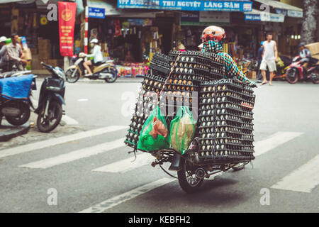 A farmer transports his eggs on a moped through the busy streets of Hanoi's Old Quarter - Stock Image