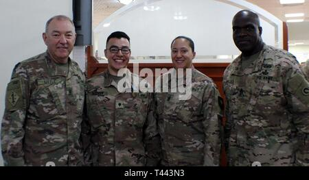 Spc. Kyle Guzman, 502d Human Resource Company, 300th Sustainment Brigade, stands with Command Sgt. Maj. Jason Little, 184th Sustainment Command, Command Sgt. Maj. Danetta Hurt, Special Troops Battalion, 300th Sustainment Brigade, and Command Sgt. Maj. Bernard Smalls, 1st Theater Sustainment Command (1TSC), during the 1TSC's Best Warrior awards dinner at Camp Arifjan, Kuwait, March 13, 2019.  Guzman finished as the runner up in the Soldier category of the competition - Stock Image