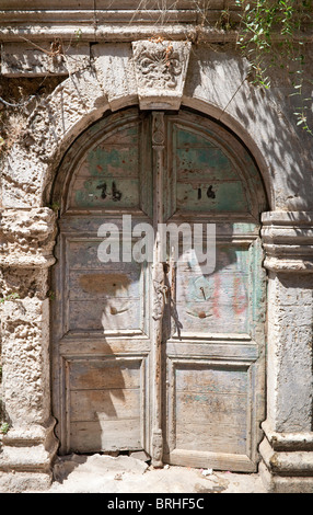 Old wooden double doors and impressive stone archway Rethymno Crete Greece - Stock Image