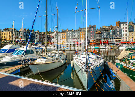 Picturesque and quaint old harbour at the Normandy village of Honfleur France with boats, sailboats, cafes and the - Stock Image