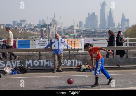 London, UK. 17th April 2019. 'Save Mother Earth', but will the goalie save the shot. Two days after Extinction Rebellion closed Waterloo Bridge turning it into a 'Garden Bridge' it remains closed to traffic despite a couple of hundred arrests. Activities continue on the bridge with new protesters arriving. Credit: Peter Marshall/Alamy Live News - Stock Image