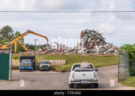 HICKORY, NC, USA-5/3/19: A Recycling center showing a large pile of metal scrap, and a pickup truck delivering aluminum cans. - Stock Image
