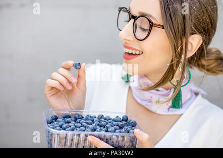 Young smiling woman eating bluberries outdoors on the gray wall background - Stock Image