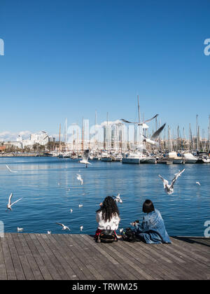 BARCELONA, SPAIN - MARCH 3, 2019: Two female tourists rest surrounded by seagulls in the old port of the city of Barcelona. Catalonia, Spain. - Stock Image