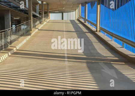concrete ramp going up in an undercover parking. - Stock Image