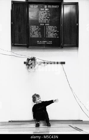 Young boy sitting on floor under war memorial at small eisteddfod in village hall at Llandudoch St Dogmaels Dyfed - Stock Image