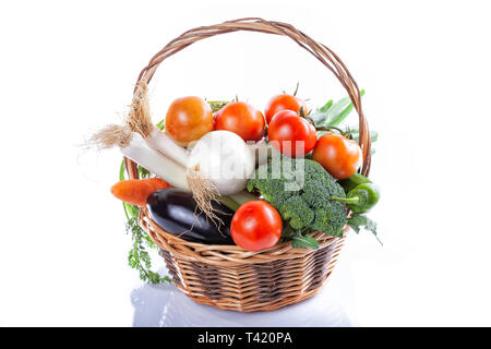 A wicker basket full of organic vegetables isolated on white. - Stock Image