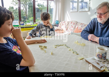 Two young brothers play a game of dominoes on a dining room table with their grandfather. - Stock Image