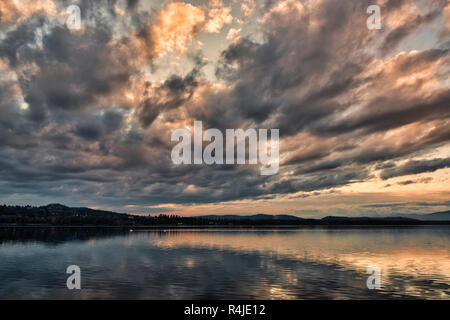 dark clouds at the sunset over the lake of Varese in a quiet autumn landscape with hills at the horizon - Stock Image