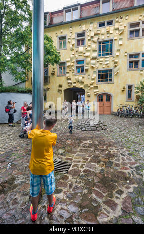 Tourists, young boy looking at rain pipe, house at Hof des Lichts (Court of the Lights), Kunsthofpassage (Art Courtyard - Stock Image