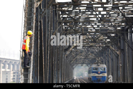 (190423) -- CHONGQING, April 23, 2019 (Xinhua) -- A worker waits for an electrical locomotive to pass on the previous Baishatuo Yangtze River railway bridge in Jiangjin of southwest China's Chongqing Municipality, April 23, 2019. The previous Baishatuo Yangtze River railway bridge, completed in 1959, will stop service after April 24. All trains will run on the new double decker steel truss cable stay railway bridge after that day. The new bridge has 4 tracks on the upper deck for passenger trains with a designed speed of 200 kilometers per hour and 2 tracks on the lower deck for cargo trains w - Stock Image