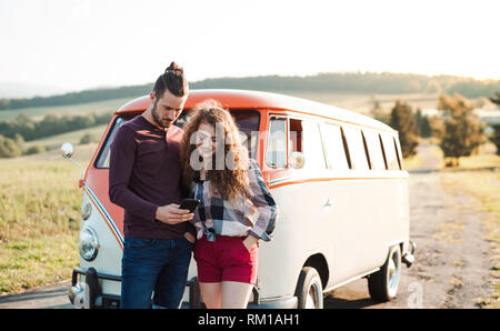 A young couple on a roadtrip through countryside, using map on smartphone. - Stock Image
