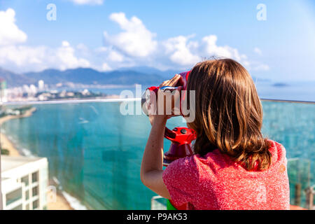 A young woman looks at the city through the tower viewer. Nha Trang, Vietnam. - Stock Image