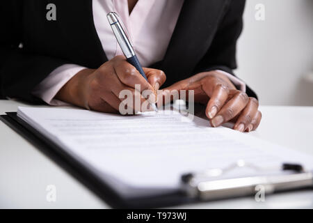 Close-up Of Businesswoman's Hand Signing On Papers Over Desk - Stock Image